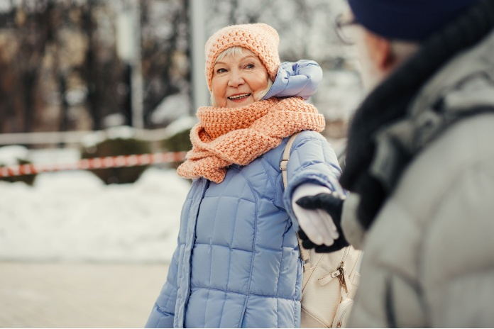Pleased aged lady smiling while husband holding her hand