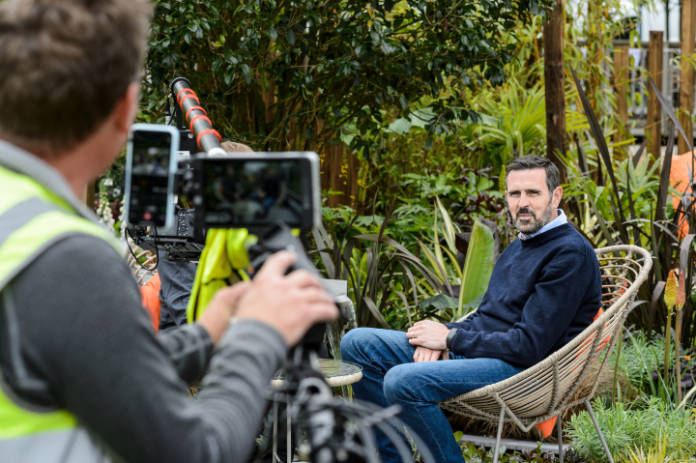 Presenter Adam Frost filming at BBC Gardeners' World Live talking about autumn plants