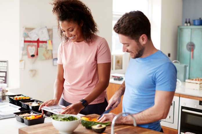 Couple Preparing Batch Of Healthy Meals At Home In Kitchen Together