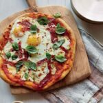 Breakfast for dinner pizza with eggs, courgette and spicy salami