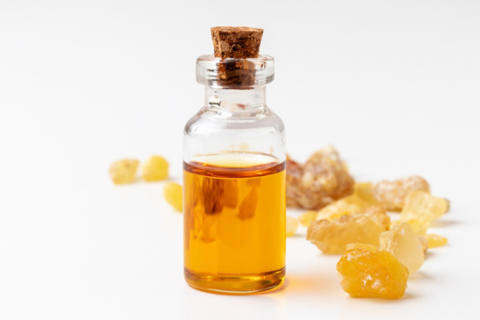 A bottle of frankincense essential oil with frankincense resin on a white background