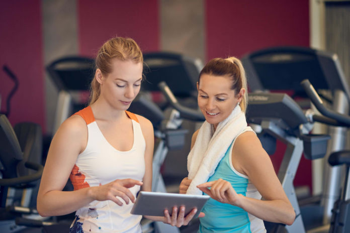 Gym anxiety- Two young women looking at tablet in gym with exercises machines in background
