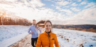 How to boost gut health- A white woman and man running outdoors on a snowy track