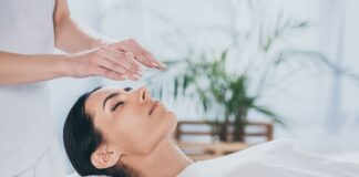 Woman with closed eyes receiving reiki treatment above head
