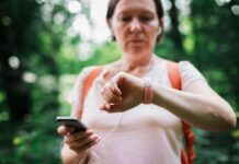 Best wearble fitness tracker-Female hiker checking fitness tracker wristband data