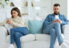 Digital detox Couple at opposite ends of sofa on their phones