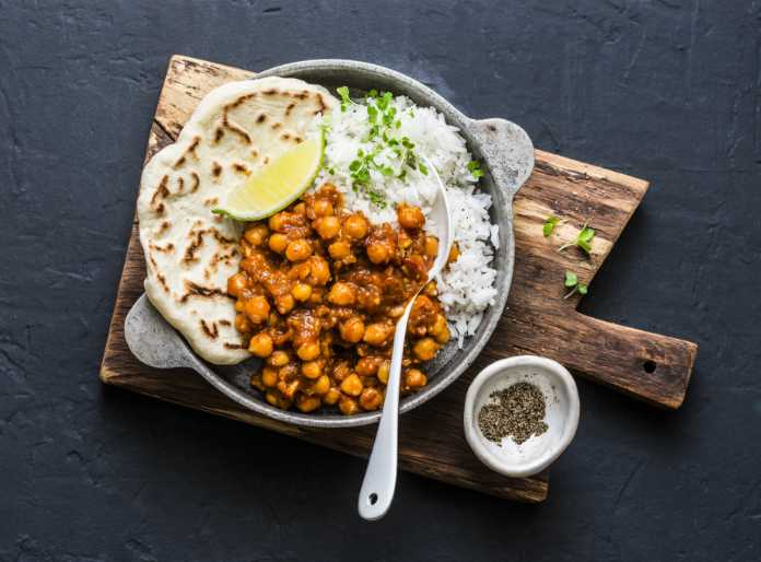 Indian spicy chickpeas curry with rice and naan bread in pan on dark background, top view. Healthy tasty vegetarian food