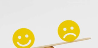 Mental health inequality- A smiley face and sad face on opposite sides of a see-saw/scale