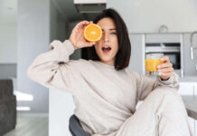 Vitamin C foods – smiling woman 30s drinking orange juice while resting in bright modern room